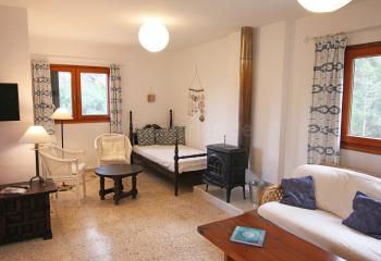 Wohnraum mit Einzelbett und Holzofen